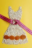 Dress shape made from oatmeal with measuring tape Royalty Free Stock Image