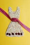 Dress shape made from oatmeal with measuring tape Royalty Free Stock Photo
