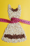 Dress shape made from oatmeal with measuring tape Royalty Free Stock Images