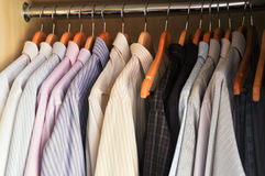 Dress shirts on hangers. Assorted color dress hanging on wooden hangers Stock Image