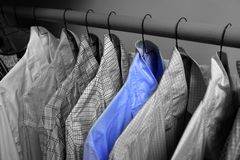 Dress Shirts Hanging on Hangers in Closet. Row of dress shirts hanging on hangers in closet choice of clothing stock photo
