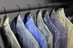 Dress Shirts Hanging on Hangers in Closet. Row of dress shirts hanging on hangers in closet choice of clothing royalty free stock photos