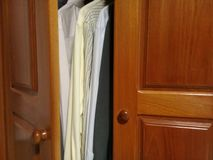 Dress shirts in the wooden closet with good light stock image
