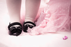 Dress and shoes for a little girl. Little black shoes on litlle feet and pink dress Stock Photography