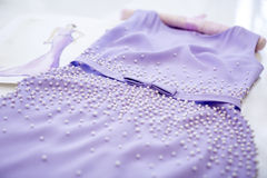 Dress and sketch paper. Beautiful lilac dress with pearls. dress and sketch paper in a sewing workshop Royalty Free Stock Photos