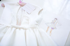 Dress and sketch paper. Beautiful white dress with pearls. dress and sketch paper in a sewing workshop Stock Photos
