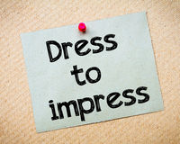 Dress to impress. Message. Recycled paper note pinned on cork board. Concept Image Royalty Free Stock Photos