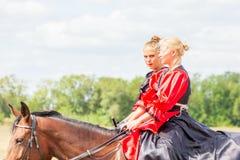 Dressage de sport équestre, passage - deux jeunes filles dans de beaux vêtements s'asseyent sur un cheval photo stock