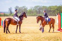Dressage de sport équestre, revue du projet - les jeunes filles dans des vêtements de jockey s'asseyent sur un cheval image stock