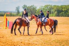 Dressage de sport équestre, revue du projet - les jeunes filles dans des vêtements de jockey s'asseyent sur un cheval photographie stock libre de droits