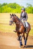 Dressage de sport équestre, revue du projet - les jeunes filles dans des vêtements de jockey s'asseyent sur un cheval photographie stock