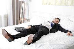 Dressed in business suit man fell asleep. On bed in light room stock image