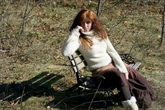 Dressed for Fall. Attractive yound redhead sitting on a bench Stock Photography