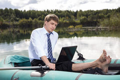 Dressed man in boat and reading. From laptop stock images