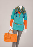 Dressed mannequin with Bag. Mannequin dressed with a scarf, T-shirt, beige pants and orange bag Stock Image