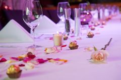 Dressed restaurant table for special occasion. Set restaurant table for special occasion with flowers, candles and chocolate Stock Photos