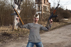 Dressed in sailor shirt man holds two guns in his hands Stock Photo