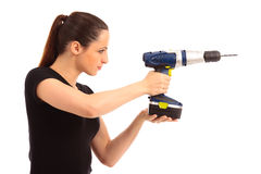 Dressed To Drill. Young female dressed in black top holding a cordless electric drill on a white isolated background Royalty Free Stock Photos