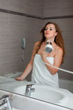 Dressed in towel beautiful woman using fen. At modern bathroom stock photo