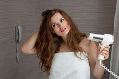 Dressed in towel beautiful woman using fen Stock Images