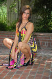 Dressed Up. A young lady poses in a colorful flowing dress on a brick platform royalty free stock images