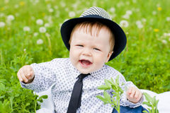 Dressed-up baby boy outdoor on grass Stock Images