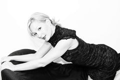 Dressed up blonde on sofa. Pretty blonde woman is kneeling on sofa smiling at you the viewer wearing fancy lace dress and hair pulled back in black and white Royalty Free Stock Image