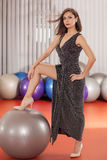 Dressed up in fitness center. Pretty young lady in evening dress posing in fitness center Stock Photography