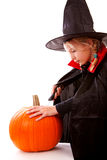 Dressed up girl is cutting pumpkin Royalty Free Stock Image