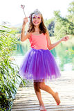 Dressed up girl with fantasy make up and magic wand. Close up full length fantasy portrait of little girl holding magic wand next to lake Stock Image