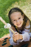 Dressed Up Little Girl Climbing A Rope Stock Image
