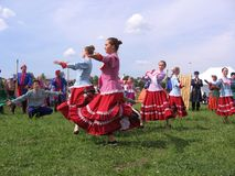 Dressed female entertainers dancing in the meadow at the village festival 2013 Kolyvan. Dressed up women artists dance perform in a clearing at the rural holiday stock photography