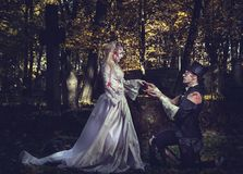 Dressed in wedding clothes romantic zombie couple. Dressed in wedding clothes romantic zombie men makes a proposal of betrothal to his zombie girlfriend Royalty Free Stock Photos