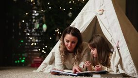 Dressed in white sweaters, mother and daughter read a fairy tale for the night lying with her in the tent of an stock video footage