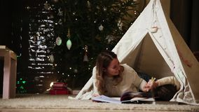 Dressed in white sweaters, mother and daughter read a fairy tale for the night lying with her in the tent of the house stock video