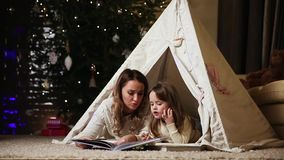 Dressed in white sweaters, my mother and daughter read a fairy tale for the night lying with her in the tent of an stock video footage