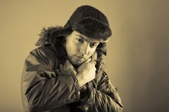 Dressed for Winter. A sepia portrait creating a vintage atmosphere of a man dressed in warm coat and hat for winter weather Stock Photo