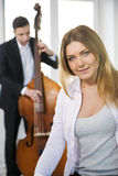 Dressed woman and contrabas player on background Stock Image