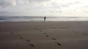 Dressed woman standing on a beach seashore, moving along shoreline. Dressed woman standing on a beach seashore, first staring at horizon and than moving along stock video footage