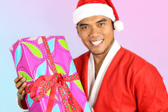 Dressed young Asian man in santa claus. On pink and blue background royalty free stock photography