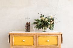 Dresser with conifer branches and Christmas decorations. Christmas decorations and conifer twigs placed on dresser with yellow drawers on background of white stock photos