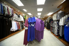 Dresses, blouses, jackets and suits in shop royalty free stock photography