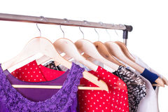 Dresses of different colors on wooden hangers Royalty Free Stock Photos