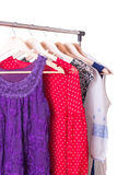 Dresses of different colors on wooden hangers Stock Photo