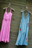 Dresses - fashion and beauty. Pink and blue dresses hanging on a wall royalty free stock image