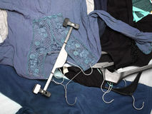 Dresses In Mess. Dresses and hangers in mess laid on the bed. Overhead cropped shot royalty free stock images
