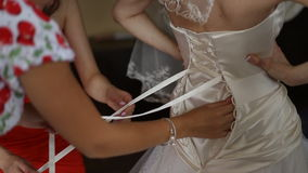 Dresses wedding dress. Bridesmaid tying bow on wedding dress stock video footage