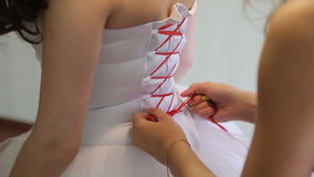 Dresses wedding dress. Bridesmaid tying bow on wedding dress stock footage