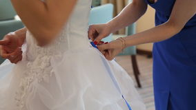 Dresses wedding dress. Bridesmaid tying bow on wedding dress stock video