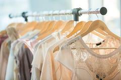 Dresses on a wooden hangers. Set of light colored dresses on a wooden hangers Royalty Free Stock Photos